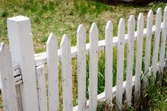Picket Fence. A white picket fence marks the edge of a lawn Stock Images