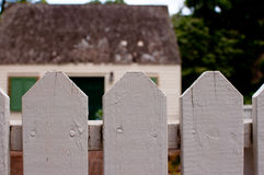 Picket Fence. A white picket fence with an old house in the background stock photo