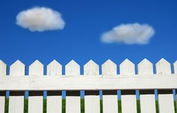 Picket fence. White picket fence, green grass and sky Royalty Free Stock Images