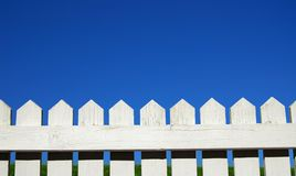 Picket fence. White picket fence, green grass and sky Stock Image