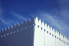 Picket fence. The corner of a picket fence and blue sky with clouds in the background stock photo