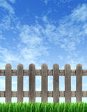 Picket Fence And Blue Sky. Picket wood fence on a blue sky with green grass in the foreground with weathered old grunge texture as a residential design element Royalty Free Stock Photography