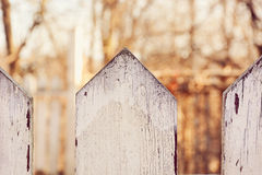 Picket Fence. Selective focus of a weathered white picket fence Stock Image