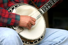 Picking. Closeup of banjo with mans hands playing stock images