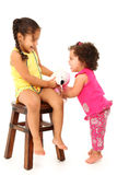 Picking on Baby Sister. Adorable 3 year old hispanic girl taking baby sister's toy away over white background Stock Image