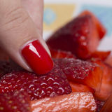 Picking cut strawberries with red nailed finger. Woman hand with red nails picking cut red strawberries Royalty Free Stock Photos