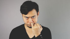 Picking his nose. An asian man with black t-shirt stock photography