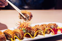 Picking Japanese grilled Unagi Maki roll with chopstick close up. Hand Picking beautiful piece Japanese grilled Unagi Maki roll with chopstick close up shot stock photos