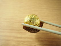 Picking a milk chocolate balls by chopsticks, covered golden aluminium foil Royalty Free Stock Photo