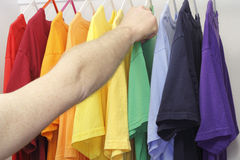 Picking Out a Shirt. Male arm and hand picking out a green t-shirt from a mixed variety of shirt colors in the closet royalty free stock images