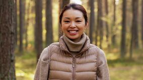 Happy smiling asian young woman in forest