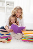 Picking a story to read with mom. Picking a story to read - little girl and her mother at home Stock Photography
