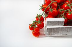 Cherry tomatoes on a branch in a wooden box on a white background. Picking tomatoes stock image