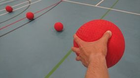 Picking up a dodgeball in my left hand royalty free stock image