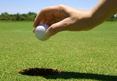 Picking up the golf ball stock photo