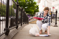 Picking up papers. Young woman picking up papers dropped in the street Stock Images