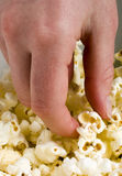 Picking up Popcorn. Hand taking a piece of popcorn from a bowl Royalty Free Stock Image