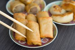 Picking up Spring Rolls with chopsticks. Golden browned spring rolls served on a traditional Chinese plate with potsticker dumplings and sausage rolls as part of royalty free stock images