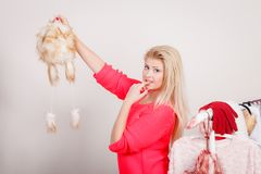 Woman in wardrobe holding furry hat. Picking winter outfit problem, clothing and fashion concept. Blonde woman in wardrobe holding furry hat, thinking what to Royalty Free Stock Photo