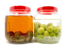 Before and after pickle plum liqueur in glass jar Stock Images