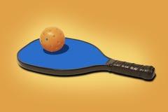 Pickleball -在蓝色桨的橙色球 免版税库存照片