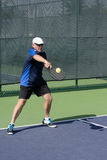 Pickleball Action - Senior Man Returning A Serve With A Backhand Stroke. Image of a senior man in a nice outfit playing pickleball.  Captured hitting a backhand Royalty Free Stock Photo