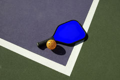 Pickleball and Blue Paddle on Edge of Court. Simple geometric image of a pickleball and a picklball paddle laying on the edge of a colorful pickleball court Stock Photography