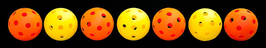 7 Pickleball Border - Orange & Yellow with Black background. Alternating line of 7 Orange and Yellow Pickleballs on a Black backgraound royalty free stock photos
