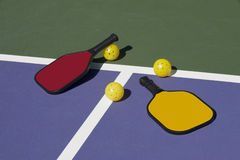 Pickleball - colorful paddles, ball and court royalty free stock photography