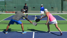 Pickleball - Mixed Doubles Action. Colorful action image of mixed double pickleball players during a game royalty free stock photos