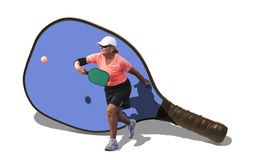 Pickleball - mujer que golpea la bola con la paleta como contexto foto de archivo