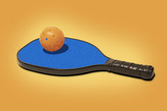 Pickleball - Orange Ball on Blue Paddle Royalty Free Stock Photos