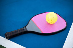 Pickleball paddle and ball. On an outdoor court Stock Photo