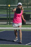 Pickleball - Smiling Female Hitting Ball At Net Royalty Free Stock Image