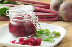 Pickled beetroot in a glass jar. Fresh beetroots on background. Close up view. stock photos