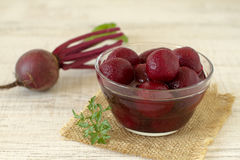 Pickled beetroots. Bowl of sour small pickled beetroot on wooden table ready for serving Stock Photo