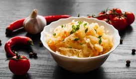 Pickled cabbage and carrots in a white bowl. On dark wooden background Royalty Free Stock Images