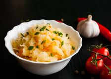 Pickled cabbage and carrots in a white bowl. On dark wooden background Royalty Free Stock Image