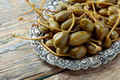 Pickled caper berries in metal dish. Edible fruits of Capparis . Berries are used as garnish.Old wooden background royalty free stock images