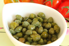 Pickled capers. Pickled caper buds in a white bowl with tomatoes at the background Stock Photography