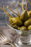 Pickled capers in a glass bowl closeup on wooden textured table. Selective focus. stock images
