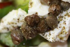 Pickled capers on Greek salad stock images