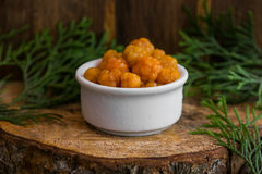 Pickled Cloudberries in a sweet syrup in a white bowl on the wooden background with the leaves of juniper.  Stock Images