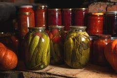 Pickled conservó los pepinos curruscantes deliciosos en tarros transparentes grandes imagen de archivo libre de regalías