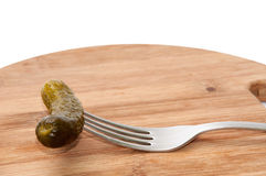 Pickled Cucumber on fork over wooden boards Stock Images