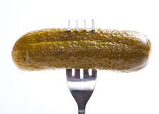 Pickled cucumber on silver fork on white background Stock Images