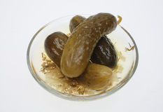 Pickled cucumber. Or sour gherkin on a cucumber leaf over white Royalty Free Stock Photos