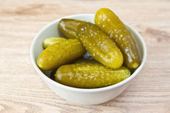 Pickled cucumbers in a bowl. On a wooden table Stock Images