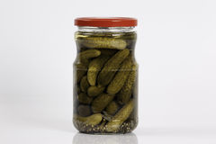Pickled cucumbers in a glass jar isolated on white Stock Images