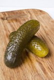 Pickled cucumbers on a kitchen cutting board Stock Image